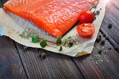 Steak of salmon with some ingredients. On a wooden textured table of a home cuisine. Healthy food concept stock images