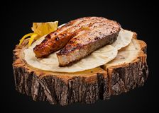 Steak from salmon on a wooden slice royalty free stock photo
