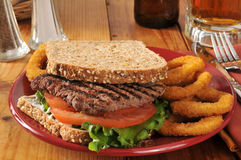 Steak sandwich. A cube steak sandwich with onion rings on sprouted nut and seed bread royalty free stock images