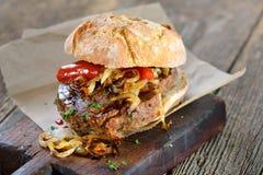 Steak sandwich. Meat sandwich: Grilled beef fillet steak with fried onion rings on a fresh roll royalty free stock image