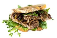 Steak-Sandwich mit karamellisierten Zwiebeln und den Kräutern lokalisiert Stockfotos