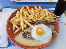 Steak on sauce with egg and fries Royalty Free Stock Photos