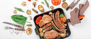 Steak and sausage cooked on grill with grilled vegetables. Steak and sausage cooked on a grill with grilled vegetables in a cast iron pan on a white background Royalty Free Stock Photography