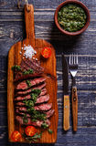 Steak served on a board with salsa verde. Steak served on a board with salsa verde, top view stock images