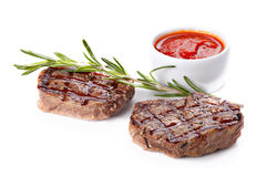 Steak  served with sauce,decorated with sprig of rosemary. Steak well done served with sauce,decorated with sprig of rosemary and spices Royalty Free Stock Photography