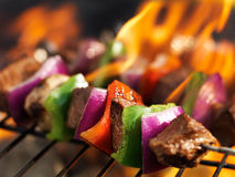 Steak shish kabobs on grill with flames. Shot close up with extreme selective focus Royalty Free Stock Photos