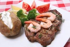 Steak and Shrimp Dinner. A steak and shrimp dinner over a plaid tablecloth Stock Photos