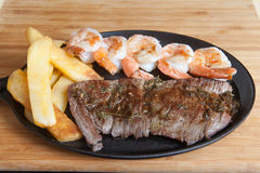 Steak shrimps french fries  skillet. Steak The flank steak is a beef steak cut from the abdominal muscles or buttocks of the cow. The cut is common in Colombia Royalty Free Stock Photography
