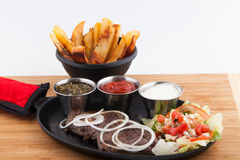 Steak shrimps french fries  skillet. Steak The flank steak is a beef steak cut from the abdominal muscles or buttocks of the cow. The cut is common in Colombia Royalty Free Stock Image