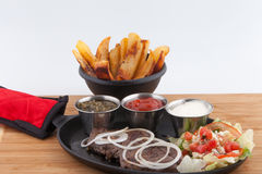 Steak shrimps french fries  skillet. Steak The flank steak is a beef steak cut from the abdominal muscles or buttocks of the cow. The cut is common in Colombia Stock Image