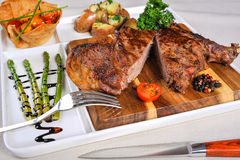 Steak and a side dish of vegetables. Beef steak with young bamboo stems, a salad of tomato and boiled potatoes Stock Photo
