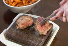 Steak sizzling on hot stone plate being sliced royalty free stock image