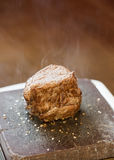 Steak sizzling on hot stone plate Royalty Free Stock Images