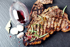 Steak with spices and glass of red wine Royalty Free Stock Photography