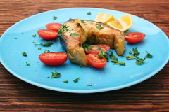 Steak of sturgeon with lemon and tomatoes Royalty Free Stock Photo