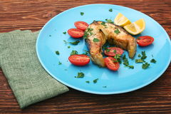 Steak of sturgeon with lemon and tomatoes Royalty Free Stock Photography