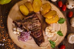 Steak t-bone on wooden backing and baked potatoes stock images