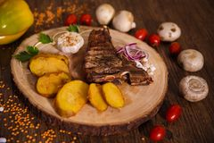 Steak t-bone on wooden backing and baked potatoes stock photos