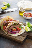 Steak tacos with sliced meet, salad and tomato salsa. On a cutting board royalty free stock photos