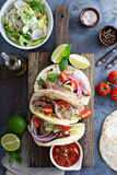 Steak tacos with sliced meet, salad and tomato salsa. On a cutting board stock photo