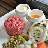 Steak tartar served with vegetables and spices Stock Photos