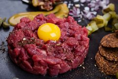 Steak tartare, gourmet delicacy raw meat starter. Minced beef dish with onion, mustard, capers and pickles served with quail egg yolk and crackers stock photography
