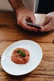 Steak tartare made of raw ground meat served on white plate. Man. Hands holding a smartphone and taking picture of steak tartare. Wooden table background Royalty Free Stock Image