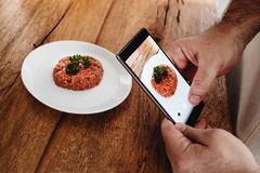 Steak tartare made of raw ground meat served on white plate. Man. Hands holding a smartphone and taking picture of steak tartare. Wooden table background Royalty Free Stock Photos
