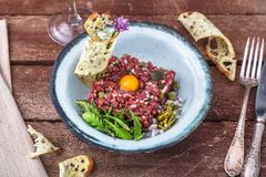 Steak tartare served with raw quail egg yolk and other tartare ingredient. Meat dish. Steak tartare served with raw quail egg yolk and other tartare ingredient Royalty Free Stock Photo