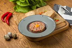 Steak Tartare. On wooden plate with ingredients Stock Image