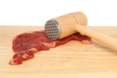 Steak and tenderiser. Siroin steak with a meat tenderising mallet on a wooden board Stock Image