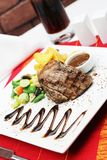 Steak tenderloin with garnish on table royalty free stock photography
