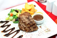 Steak tenderloin with garnish on table royalty free stock photo