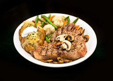 Steak. A thick cut juicy grilled steak with vegetables and potato, covered in sauteed mushrooms stock photos