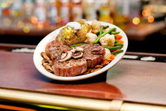Steak. A thick cut juicy grilled steak with vegetables and potato, covered in sauteed mushrooms Stock Photography