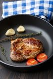 Steak with thyme, tomato and garlic. Royalty Free Stock Photography