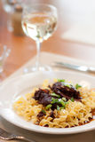 Steak tips and pasta with wine. An elegant dinner of wavy egg noodles topped with steak tips and chopped green onions sits with a refreshing glass of cold white Stock Images
