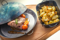 Steak with tomatoes and baked potatoes, metal pan, dinner or lunch food, restaurant Stock Photos