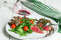 Steak and tomatoes on a plate. Grilled meat with salad and vegetables Royalty Free Stock Images