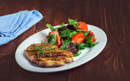 Steak and tomatoes on a plate. Grilled meat with salad and vegetables Stock Photography