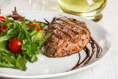Steak and tomatoes on a plate. Grilled meat with salad and vegetables Stock Image