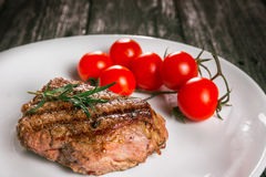 Steak and tomatoes on a plate. Grilled meat with salad and vegetables Stock Photos