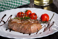 Steak and tomatoes on a plate. Grilled meat with salad and vegetables Stock Images