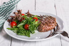 Steak and tomatoes on a plate. Grilled meat with salad and vegetables Royalty Free Stock Photos