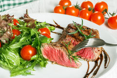 Steak and tomatoes on a plate. Grilled meat with salad and vegetables Royalty Free Stock Image