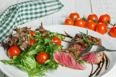 Steak and tomatoes on a plate. Steak and salad on a plate Stock Photo
