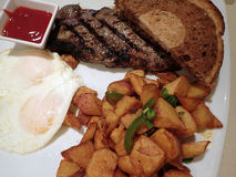 Steak with two eggs over easy, two slices of rye bread, potatos Stock Photos