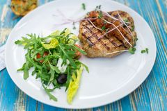 Steak with vegetable salad and herbs on a white plate. On whole frame. Horizontal frame Royalty Free Stock Images