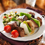 Steak and vegetable shishkabobs with cucumber salad Royalty Free Stock Images