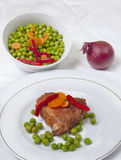 Steak with vegetables. Sirloin steak with peas,red onion,pepper strips and carrots, on white plate Royalty Free Stock Image